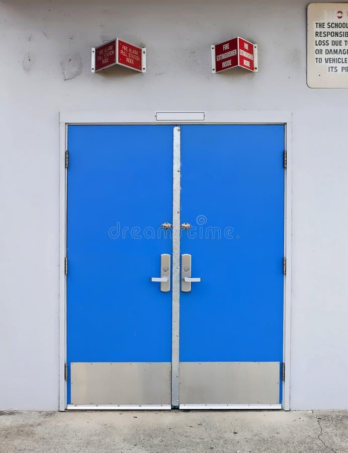 Puerta de la escuela del viejo estilo con la alarma de incendio arriba imagenes de archivo