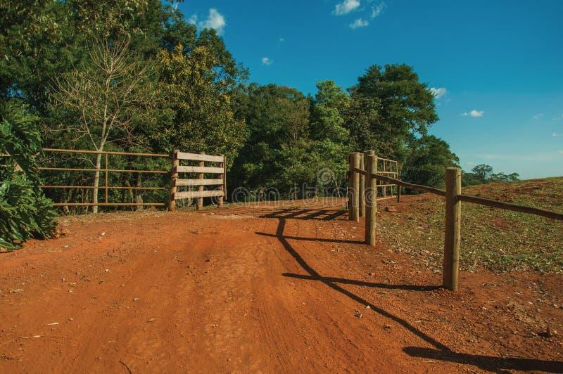 Puerta de la granja con el guardia de ganado y la cerca del alambre de púas foto de archivo libre de regalías