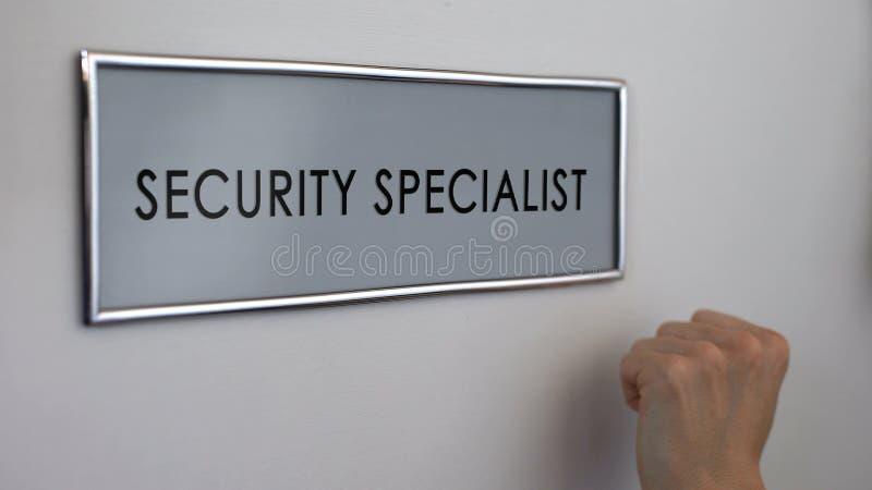 Puerta de la oficina del especialista de la seguridad, mano que golpea, servicio de protección del negocio fotografía de archivo libre de regalías
