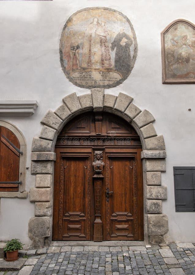 Puerta de madera adornada con el golpeador del metal y Virgen María de la pintura de pared con el bebé coronado Jesús, Cesky Krum imagenes de archivo
