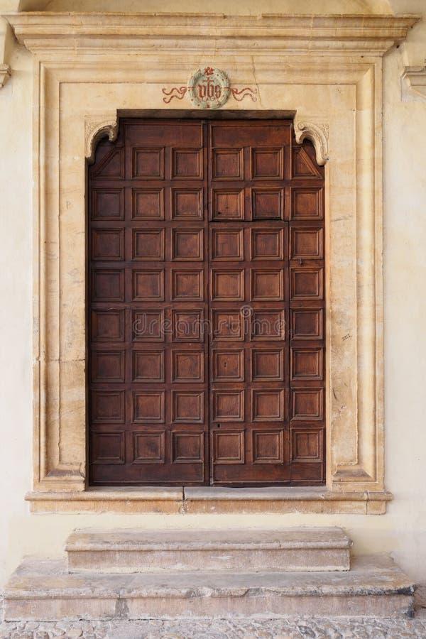 Puerta de madera adornada vieja de una iglesia medieval italiana en Spello imagen de archivo