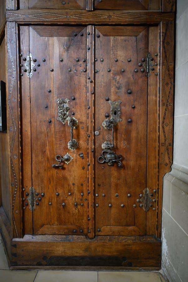 Puerta de madera antigua de la sacristía con el cráneo y la serpiente en el montaje de la puerta, santo Michael Church Schwabisch fotos de archivo
