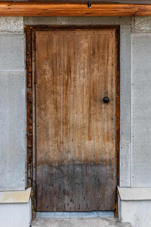 Puerta de madera cerrada vieja Una peladura, puerta agrietada, marrón clara foto de archivo