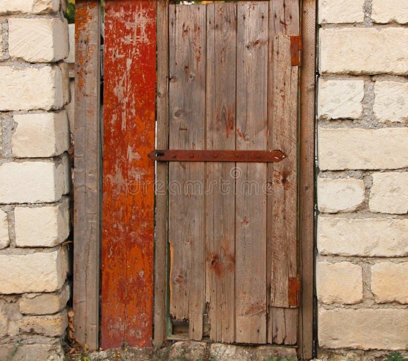 Puerta de madera con la pared de ladrillo vieja de la cerradura de puerta imágenes de archivo libres de regalías
