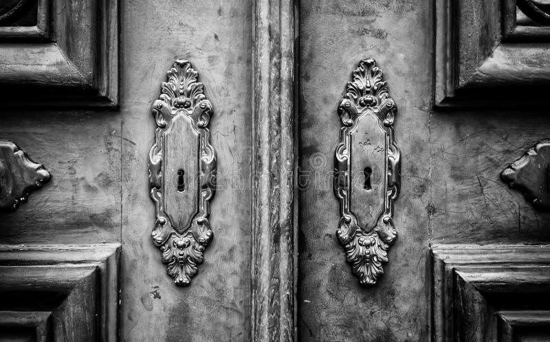 Puerta de madera con los golpeadores del metal imagenes de archivo