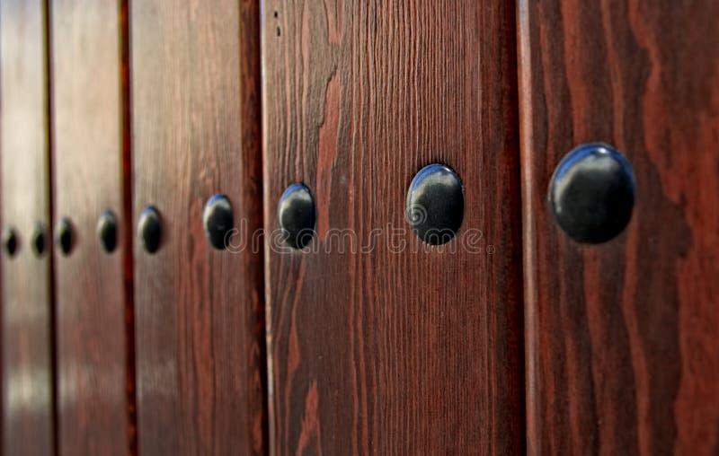 Puerta de madera con los remaches negros del hierro imagen de archivo libre de regalías