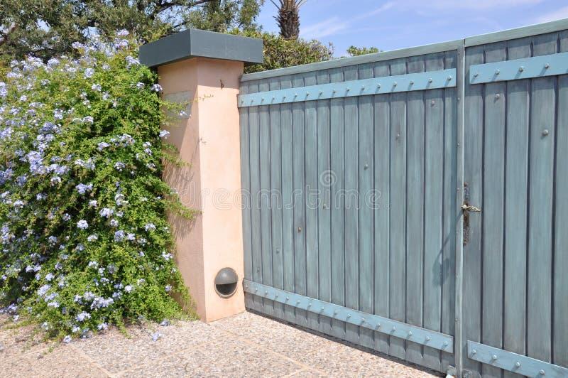 Puerta de madera con un arbusto verde grande fotografía de archivo libre de regalías