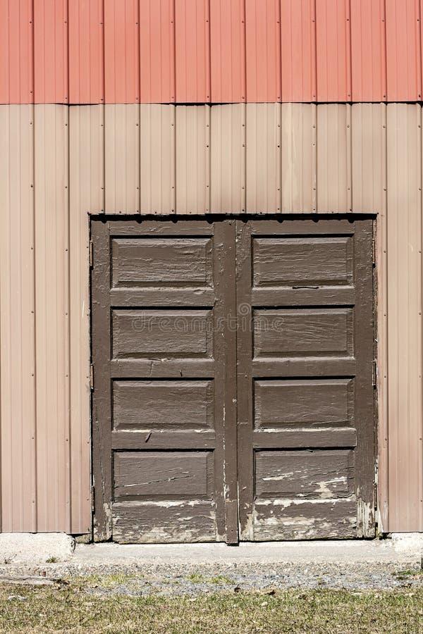 Puerta de madera de Brown ocultada en el lado del edificio del metal imágenes de archivo libres de regalías