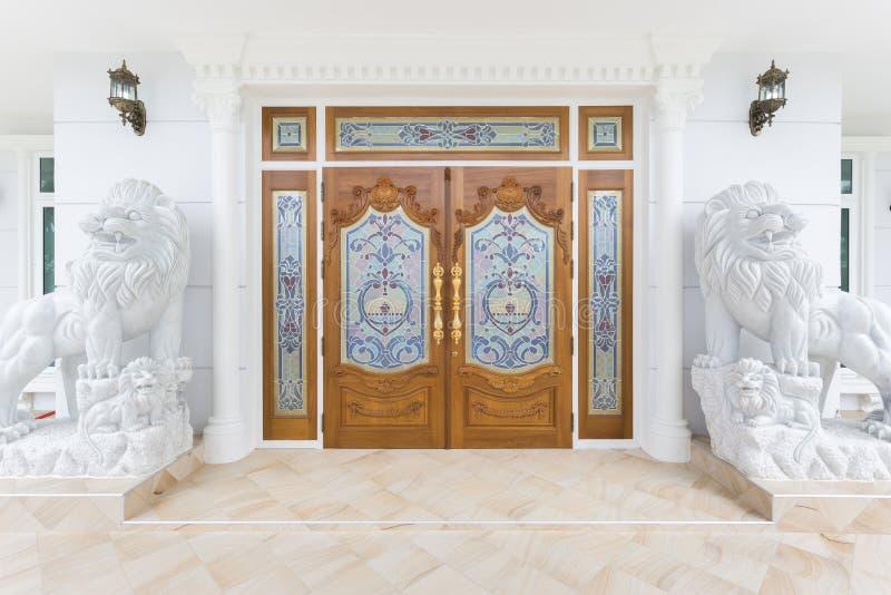 Puerta de madera de la teca con la estatua blanca de los leones fotos de archivo