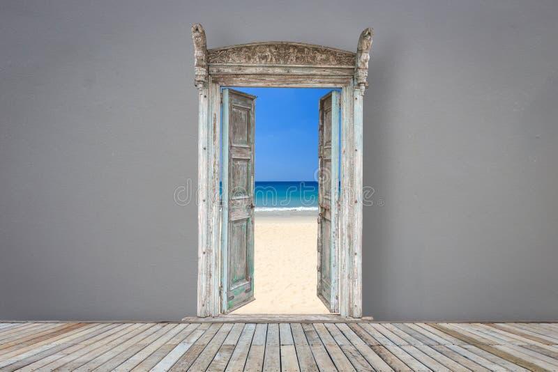 Puerta de madera del estilo retro en el sitio gris del color abierto en la playa imagenes de archivo