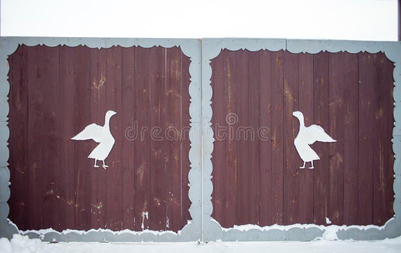 Puerta de madera en estilo ruso tradicional y nieve alrededor en día de invierno Figuras talladas de los animales y de los pájaro fotografía de archivo libre de regalías