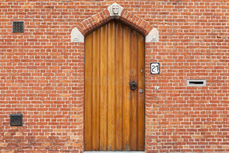 Puerta de madera en la pared de ladrillo de la casa en Brujas, Bélgica foto de archivo