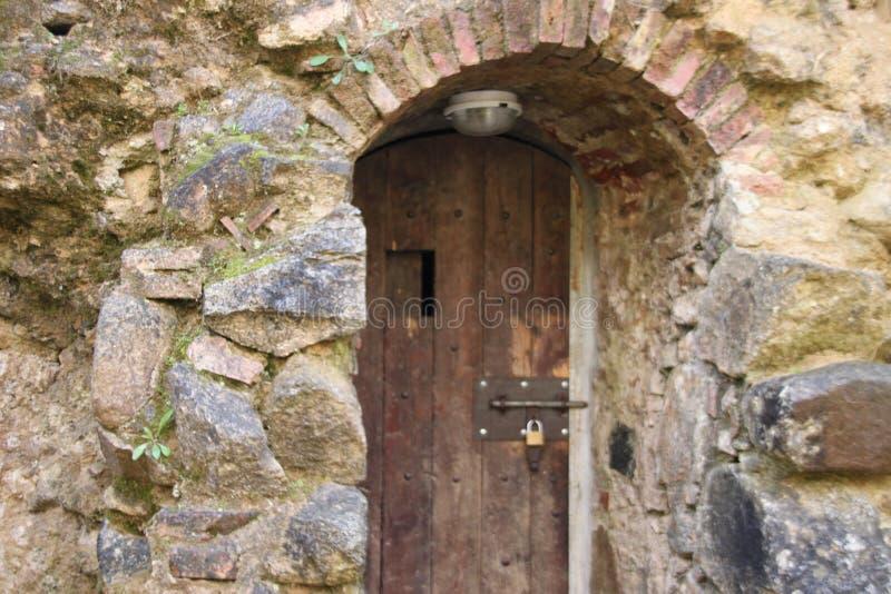 Puerta de madera en la torre de piedra imágenes de archivo libres de regalías
