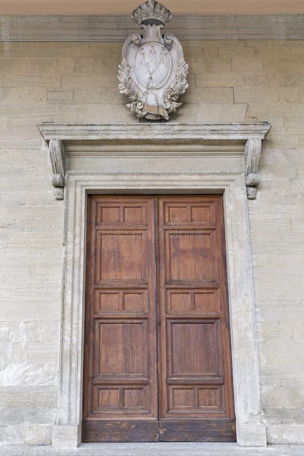 Puerta de madera grande con el escudo de armas en San Marino imágenes de archivo libres de regalías