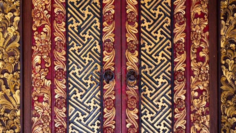 Puerta de madera indonesia maravillosamente adornada en rojo negro y oro imagen de archivo libre de regalías