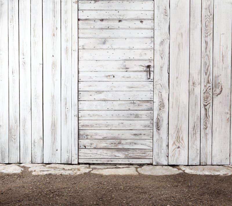 Puerta de madera lamentable vieja blanca en la pared de madera envejecida, exterior de a imagen de archivo