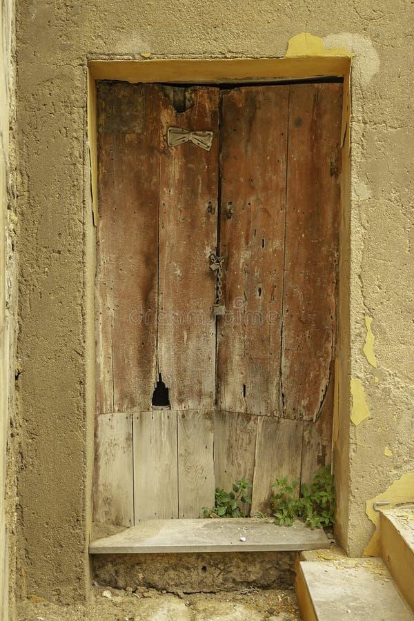 Puerta de madera marrón descolorada dañada vieja interesante con un cierre del edificio de piedra abandonado en Sicilia fotografía de archivo libre de regalías