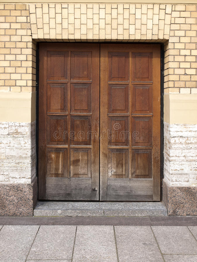 Puerta de madera marrón vieja integrada en una pared de ladrillo amarilla imagenes de archivo