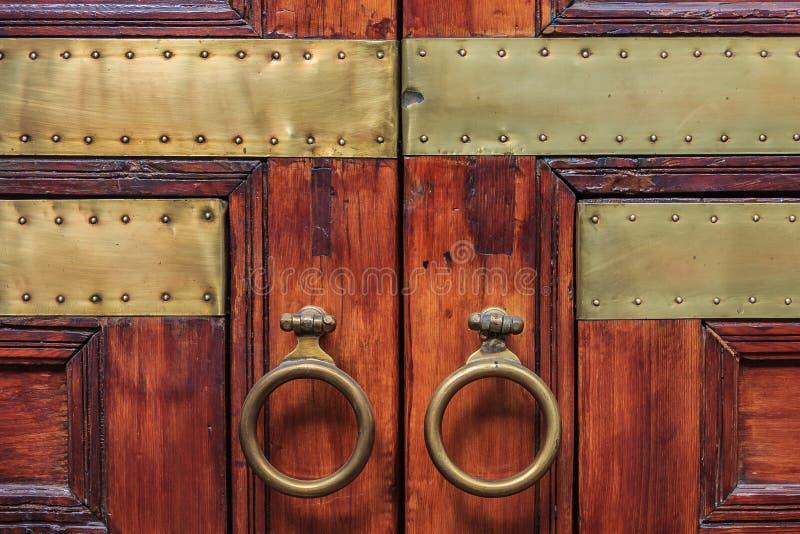 Puerta de madera marroquí adornada en un riad foto de archivo