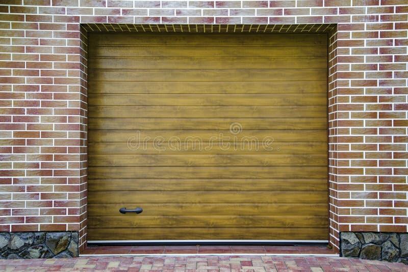 Puerta de madera oscura del garaje con el fondo coloreado de la pared de ladrillo fotos de archivo libres de regalías