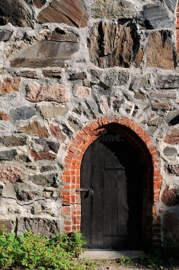 Puerta de madera oscura vieja en la pared de piedra foto de archivo