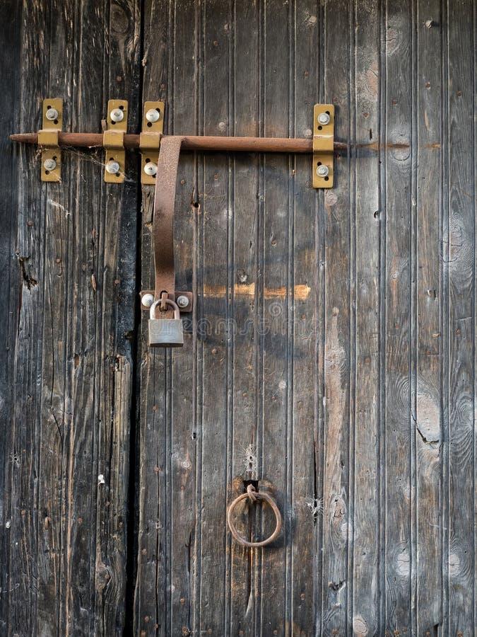 Puerta de madera rústica con el candado y el cierre oxidados fotos de archivo