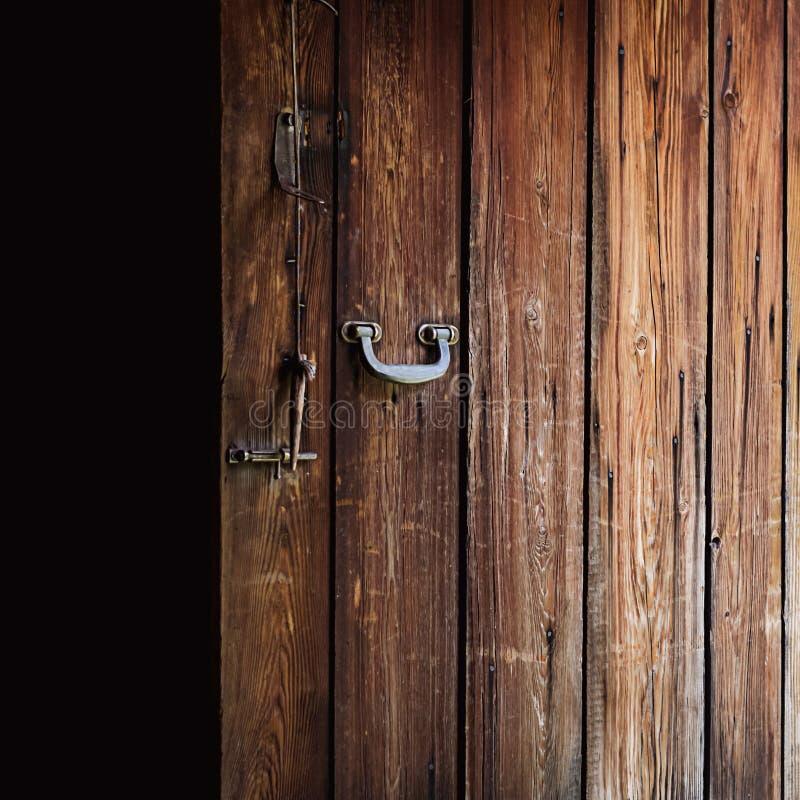 Puerta de madera resistida vieja abierta con la manija pulida del metal, el cierre de acero y la ejecución de madera del perno en fotos de archivo libres de regalías