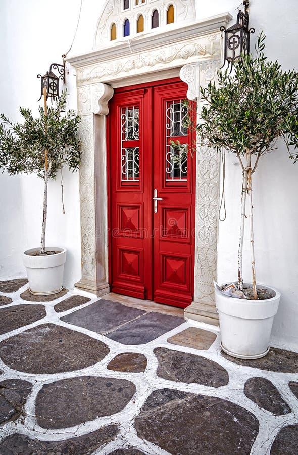 Puerta de madera roja adornada con las palmeras en Mykonos, Grecia fotos de archivo libres de regalías