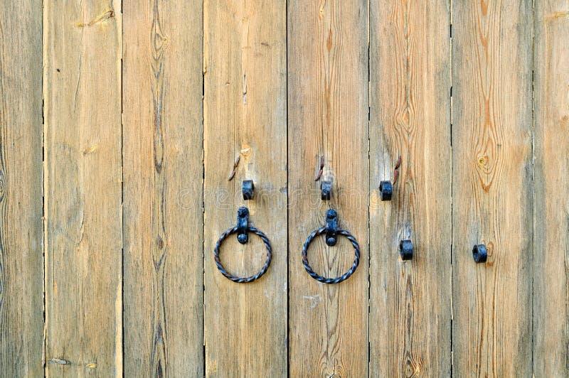 Puerta de madera texturizada vieja con los tiradores de puerta envejecidos del metal bajo la forma de anillo foto de archivo
