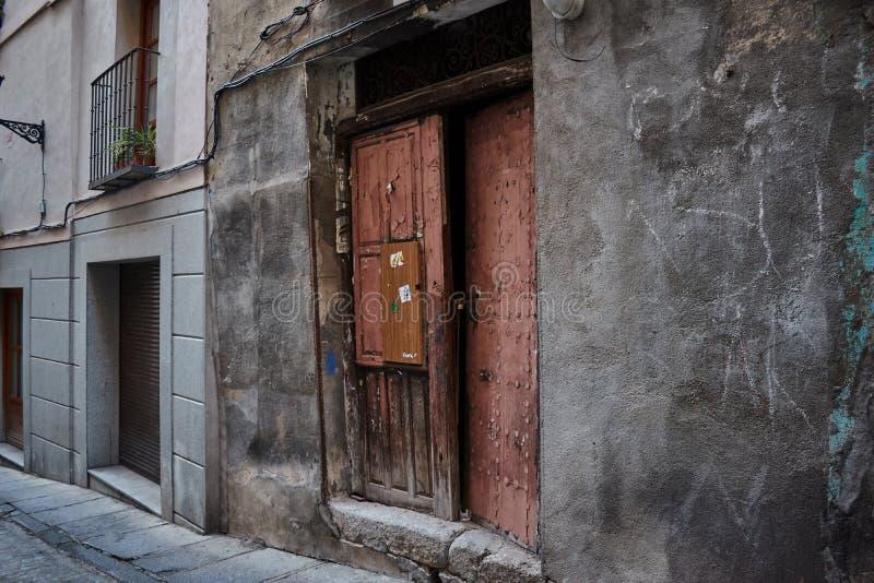 Puerta de madera vieja al lado de la construcción moderna de la casa en Toledo, España Fondos agradables imágenes de archivo libres de regalías