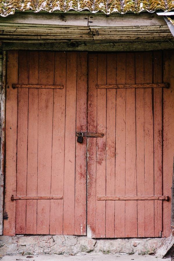 Puerta de madera vieja cerrada en la cerradura Pintura de la peladura Casa granero imagenes de archivo