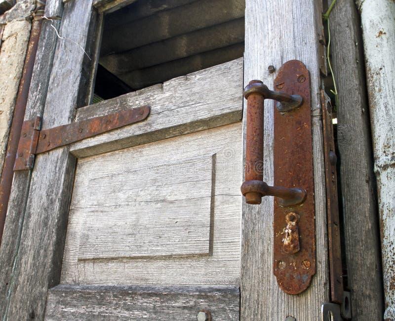 Puerta de madera vieja con el botón oxidado foto de archivo