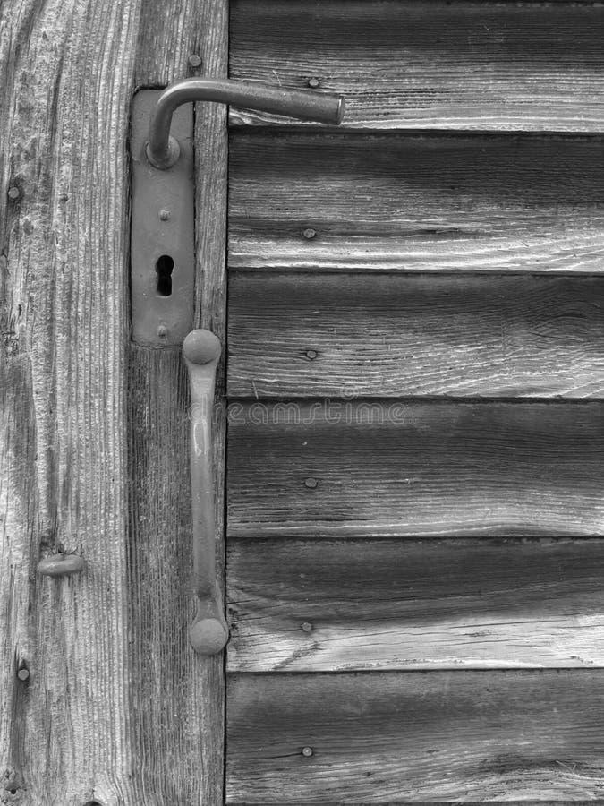 Puerta de madera vieja con el tirador de puerta en blanco y negro fotos de archivo