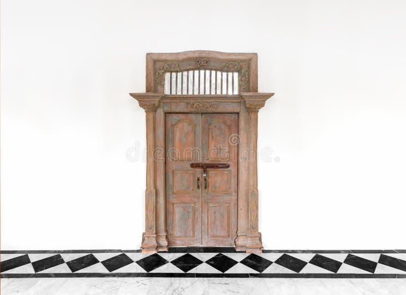 Puerta de madera vieja en el fondo concreto blanco de la pared del cemento imagen de archivo