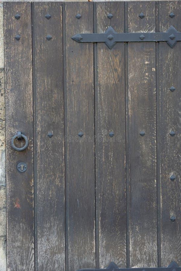 Puerta de madera vieja en la pared de piedra a partir de la era medieval Candado del metal del vintage en una puerta de madera foto de archivo
