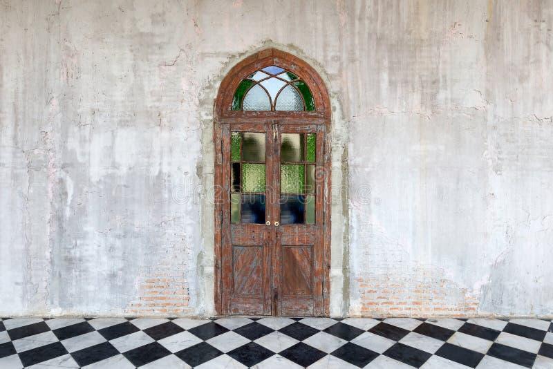 Puerta de madera vieja en un fondo concreto de piedra de la pared del cemento fotos de archivo