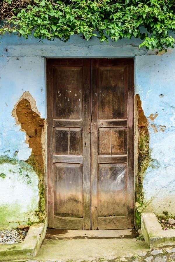 Puerta de madera vieja y pared azul dilapidada fotografía de archivo
