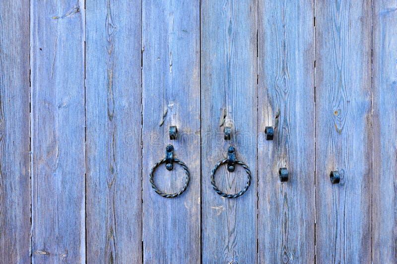 Puerta de madera violada clara texturizada vieja con los tiradores de puerta envejecidos del metal bajo la forma de anillo imagen de archivo libre de regalías
