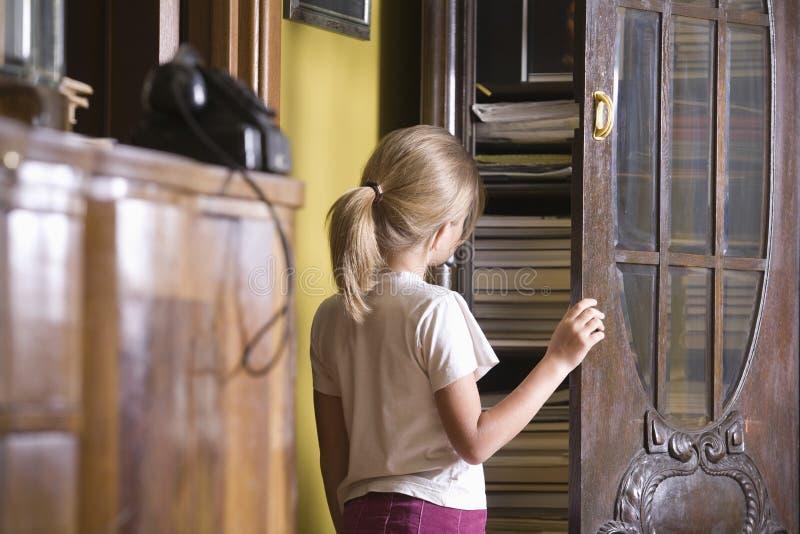 Puerta del armario de la abertura de la muchacha imagen de archivo