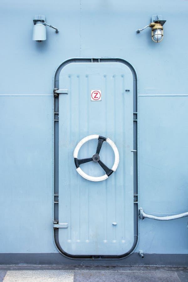 Puerta del hierro del acorazado con la cerradura del volante y el fondo de la bombilla imagen de archivo libre de regalías