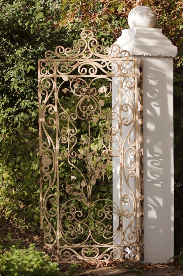Puerta del hierro labrado con la pared blanca en un jardín foto de archivo