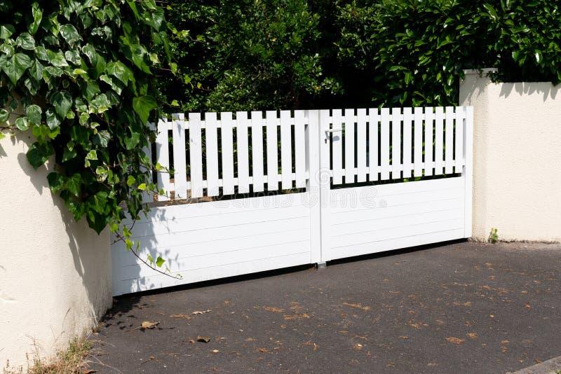 Puerta del jardín de la puerta del PVC y casa blancas del domicilio familiar imagenes de archivo