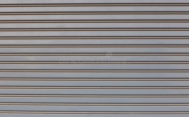 Puerta del laminado de acero de la tienda o de la tienda, vista delantera La puerta del garaje tiene dos manijas abiertas y un oj imagen de archivo