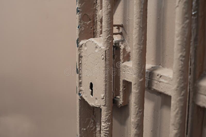 Puerta del metal con las barras en la cárcel con la cerradura imagenes de archivo