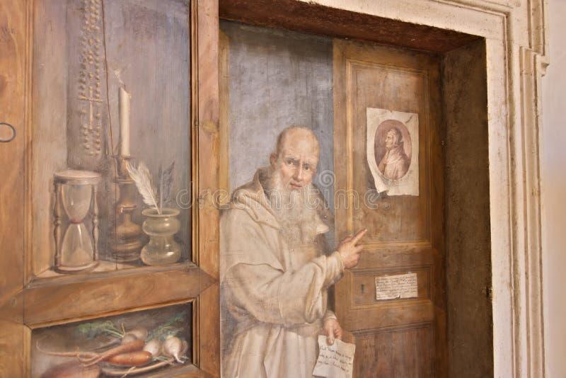 Puerta del monasterio pintada con la figura de un fraile fotografía de archivo libre de regalías