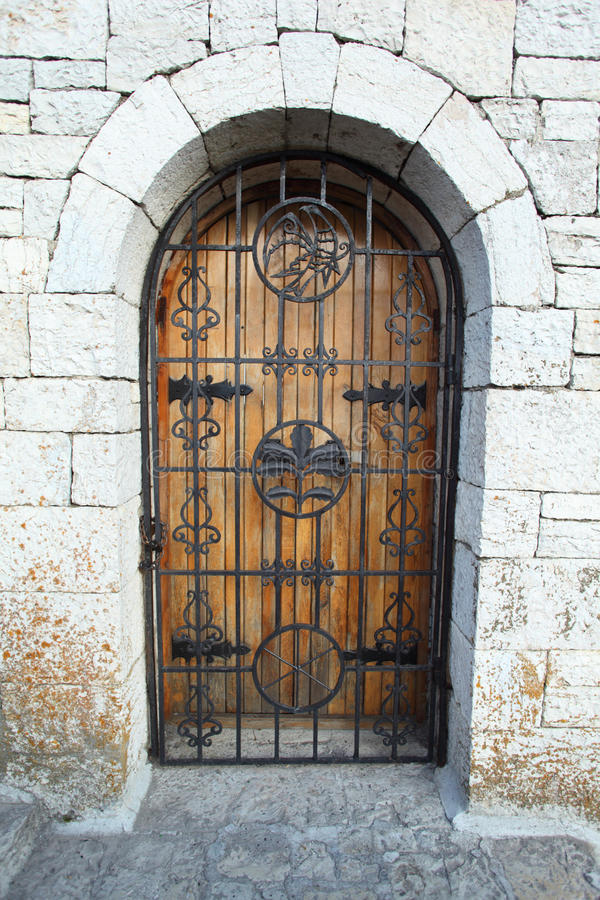 Puerta detrás del cedazo en la pared de piedra imagen de archivo libre de regalías