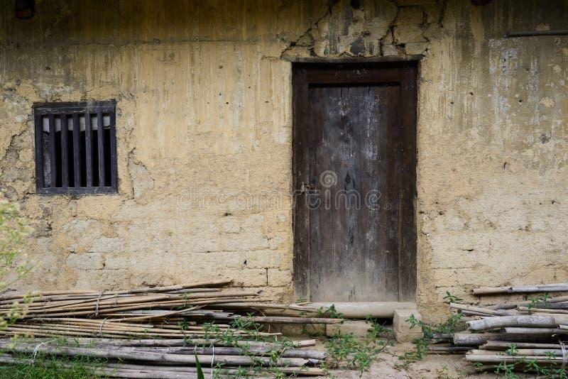 Puerta dilapidada en pared de tierra de la casa china antigua imagen de archivo libre de regalías