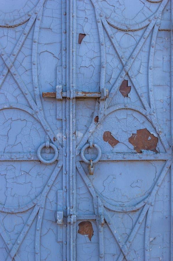 Puerta forjada vieja del hierro con los remaches y la peladura de la pintura azul fotos de archivo libres de regalías