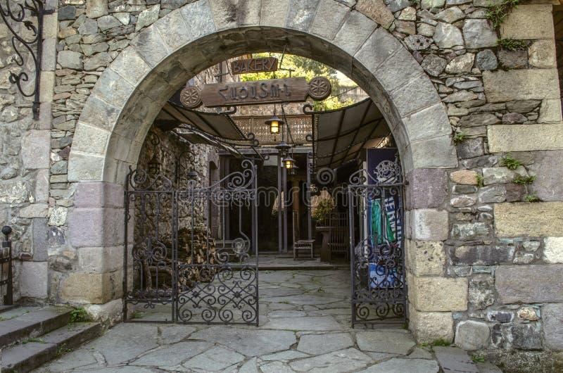 Puerta hermosa del hierro labrado con el arco de piedra en la entrada a la panadería en la calle de Sharambeyan en el museo Dilij imagen de archivo libre de regalías