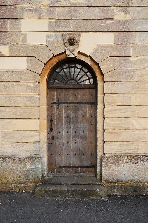 Puerta lateral de la iglesia con el cráneo y los huesos imagen de archivo libre de regalías